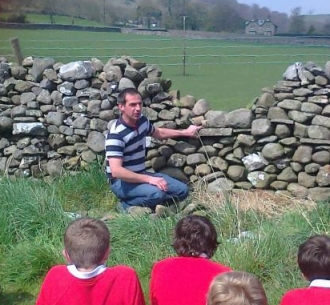 Peter Halliday, a dry stone waller, demonstrating the ancient art of walling to Year 8 students at Settle Middle School